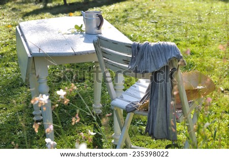 Wooden garden furniture in the grass of a garden in the countryside - stock photo