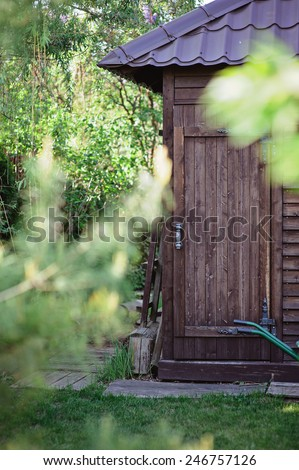 wooden garden shed with door in summer sunny day
