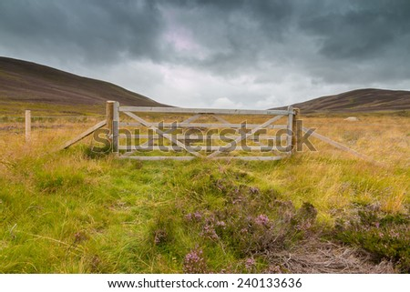 Wooden gate and wire fence on a meadow between hills in the Highlands of Scotland, UK
