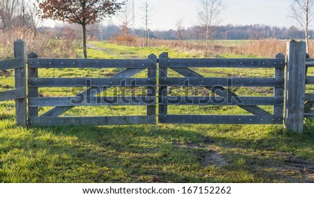 Wooden gate close with a cable and a padlock seen in backlight. - stock photo