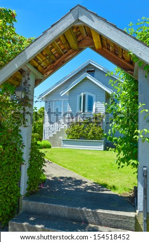 Wooden gate leading to small North American house. Look through the gate to small family house.