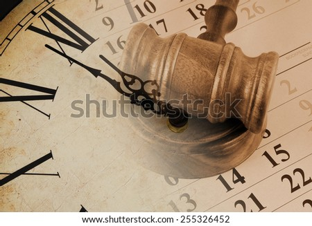 Wooden gavel and clock on paper calendar  - stock photo