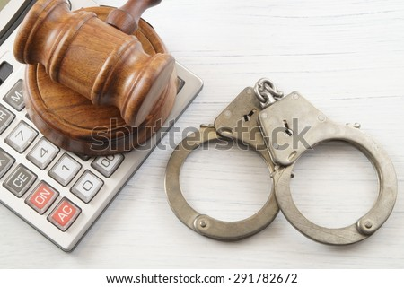 Wooden gavel, calculator and handcuffs on white table. financial fraud concept - stock photo