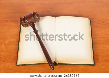 Wooden gavel from the court and opened law book on wooden background. Shallow DOF - stock photo