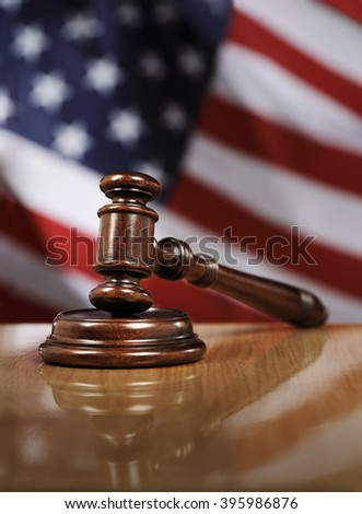 Wooden gavel on glossy table, The flag of USA in the background. - stock photo