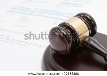 Wooden gavel over some financial documents - stock photo