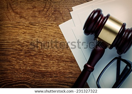 Wooden gavel with a brass band and glasses on notepaper conceptual of a judgement in law, justice or an auctioneers gavel, view from above on a wooden desk with copyspace - stock photo