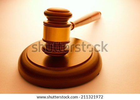 Wooden gavel with a brass band resting on a plinth used by a judge or auctioneer and conceptual of justice and judgements with backlit highlight and copyspace - stock photo