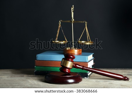 Wooden gavel with justice scales and books on black background - stock photo