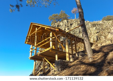 wooden gazebo in the mountains against the blue sky - stock photo