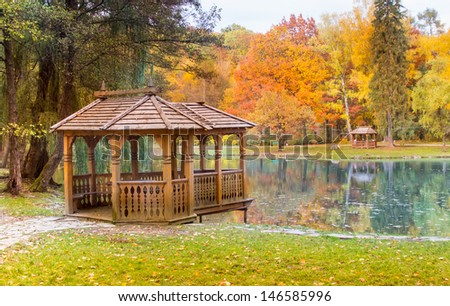 wooden gazebo on the lake in the autumn park - stock photo