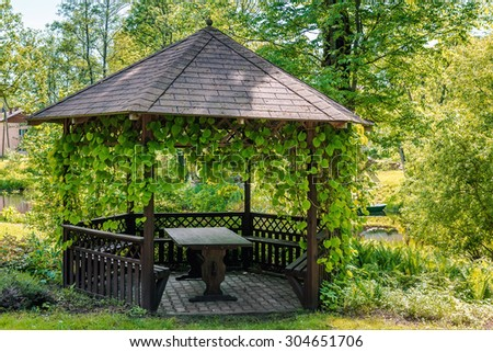 Wooden gazebo over summer landscape - stock photo