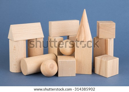 wooden geometric shapes on a blue background - stock photo