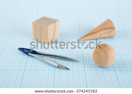 Wooden geometric shapes on graph paper - stock photo