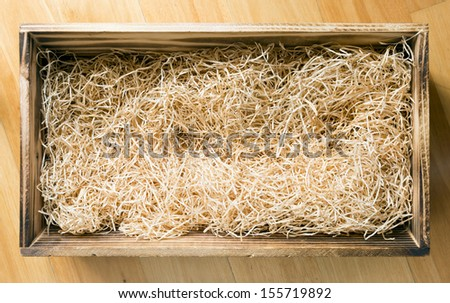 Wooden gift or display box filled with natural raffia or twine - stock photo