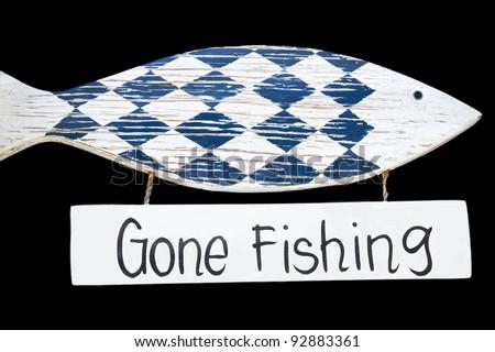 Wooden gone fishing sign, isolated on black background - stock photo