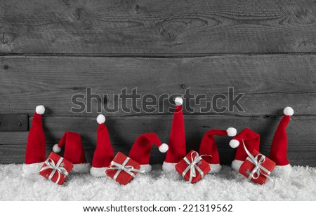 Wooden grey christmas background with red santa hats and gifts. - stock photo