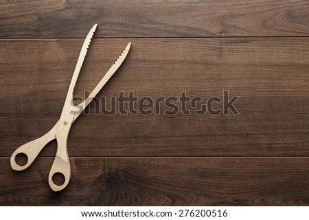 wooden grill tongs on the brown table - stock photo