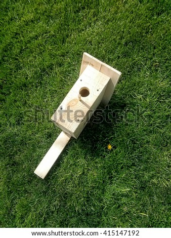 Wooden hand made birdhouse on a green grass