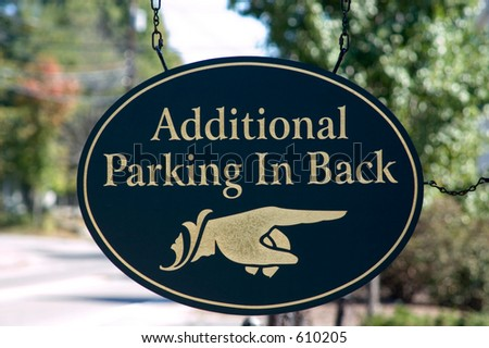 Wooden hand sign pointing to additional parking - stock photo