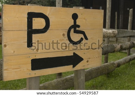Wooden Handicapped Parking Only arrow sign. Permit Parking sign For disabled person. - stock photo