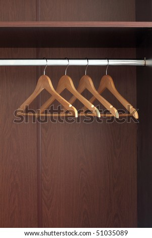 Wooden hanger hanging in an empty closet on the upper - stock photo