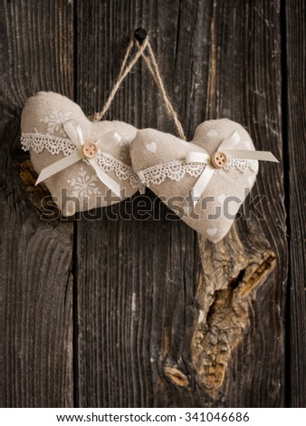 wooden heart hanging on a branch against white wooden planks - stock photo
