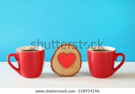 Wooden heart next to coffee cups on wooden table.