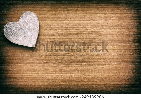 Wooden heart on a faded grunge wooden background - stock photo