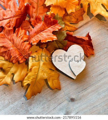 Wooden Hearts and Autumn Leaves on Wooden Background as seen from Above - stock photo