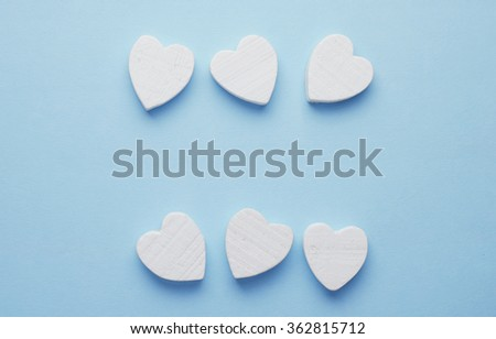 Wooden hearts organized in a row over blue background with negative space, top view