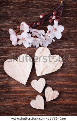 Wooden hearts placed nicely with spring cherry blossom flowers on a vintage wood background - stock photo