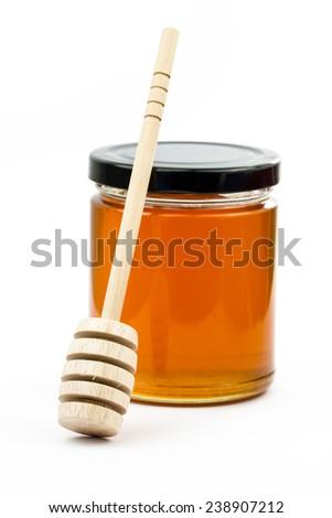 wooden honey dipper with honey jar   - stock photo