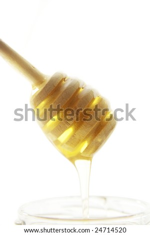 Wooden honey drizzler with a  honey isolated on white.