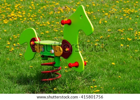 Wooden horse toy in a park. Children love to play with it, because it goes back and forth when you swing