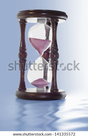wooden hourglass with pink sand are on a blue background