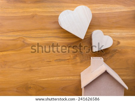 wooden house and heart on brown wood background - stock photo
