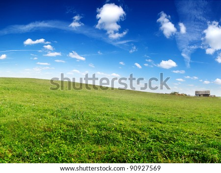 Wooden house at the foot of green hill. - stock photo