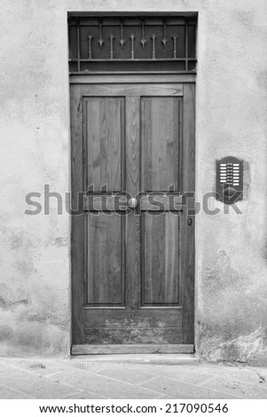 Wooden, house door in Tuscany region  (black and white) - stock photo