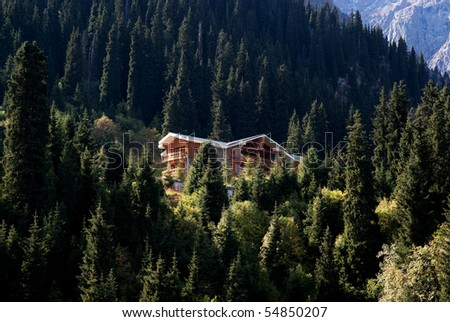Wooden house in a mountain forest - stock photo