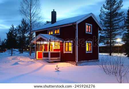 wooden house in Sweden during winter by night - stock photo