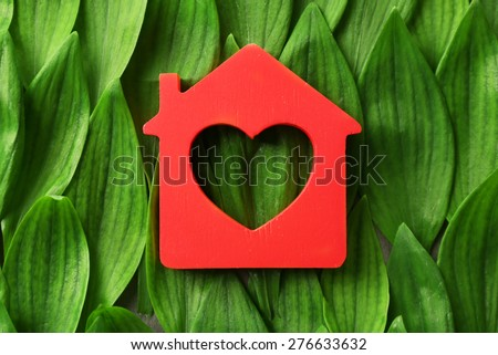 Wooden house on green leaves background - stock photo