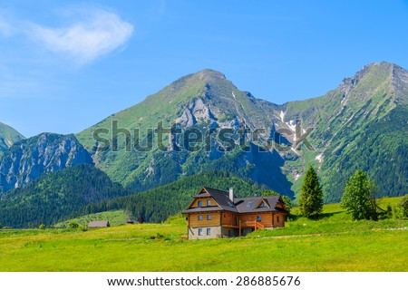 Wooden house on green meadow with Tatry Bielskie Mountains in background in summer, Slovakia - stock photo