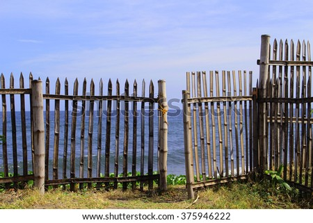 Wooden house on the beach, look through rustic fence to the ocean. Tropical island lifestyle. Seascape from a filipino village. Bamboo gate to sea. Seaside life of Negros Oriental island, Philippines