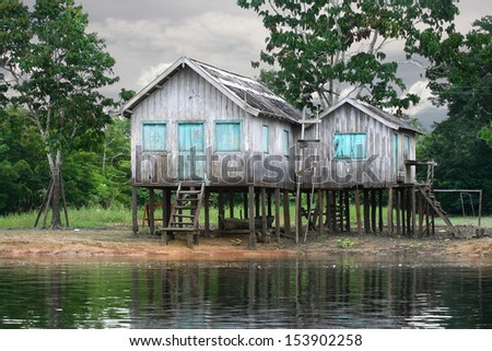 Wooden house on the river bank, Amazon River, rainy season, Brazil.