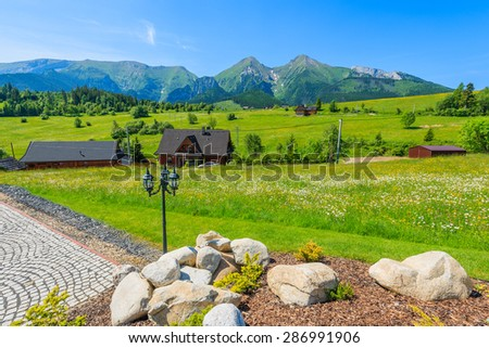 Wooden houses on green meadow with blooming flowers with Tatry Bielskie Mountains in background in summer, Slovakia - stock photo