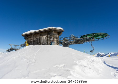 wooden hut and ski lift in mountain - stock photo