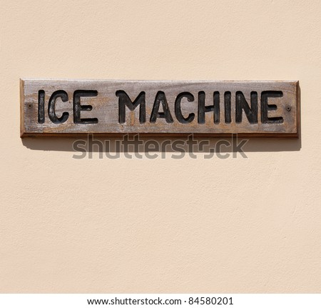 wooden ice machine sign on a pink wall (usual at tropical resorts)