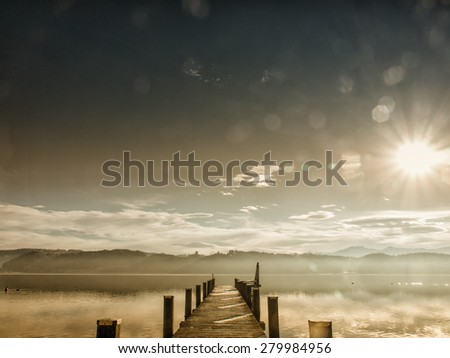 wooden jetty at a little lake in upper bavaria with mountains in background - stock photo