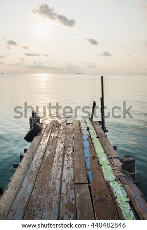 Wooden jetty bridge with seascape during sunrise at Ao Lung Dam beach in Samet island, Thailand. - stock photo